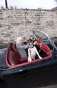 Older woman driving convertible with dog - BLEF05771