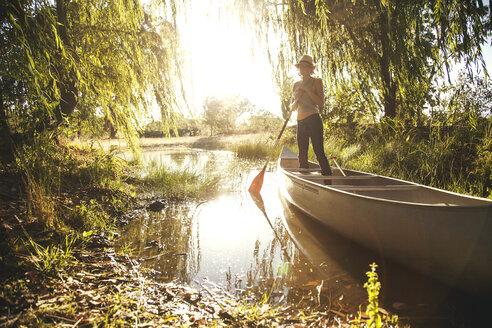 Caucasian woman rowing canoe in rural creek - BLEF05810