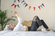 Happy woman lying on bed at home taking a selfie - FBAF00688
