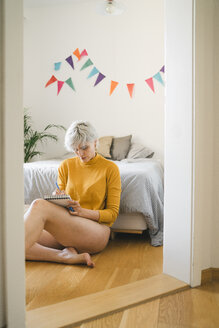 Woman sitting next to bed at home taking notes - FBAF00700