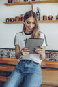 Portrait of young woman smiling using a tablet in a cafe - ACPF00521