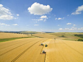 Scenic aerial landscape view of combine harvesters and tractor trailer in sunny golden barley field in rural countryside - JUIF01156
