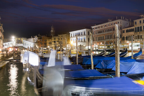 Covered moored gondolas in front of illuminated architectural buildings in the Grand Canal at night, Venice, Italy - JUIF01165