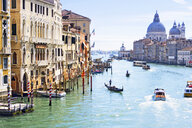 Gondolas and boats in sunny Grand Canal in front of Santa Maria della Salute and architectural buildings in Venice, Italy - JUIF01168