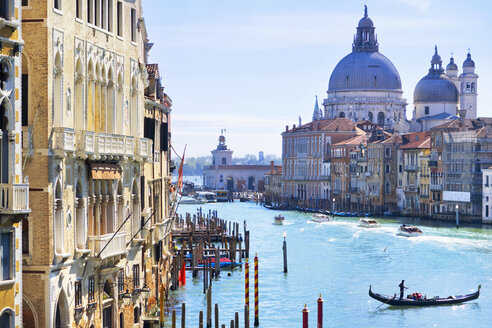 Gondolas and boats in sunny Grand Canal in front of Santa Maria della Salute and architectural buildings in Venice, Italy - JUIF01174