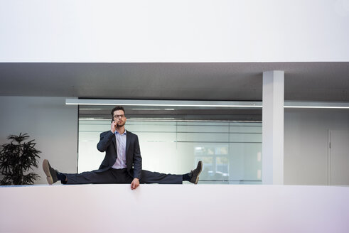 Businessman doing the splits on reception desk in office talking on cell phone - MOEF02182