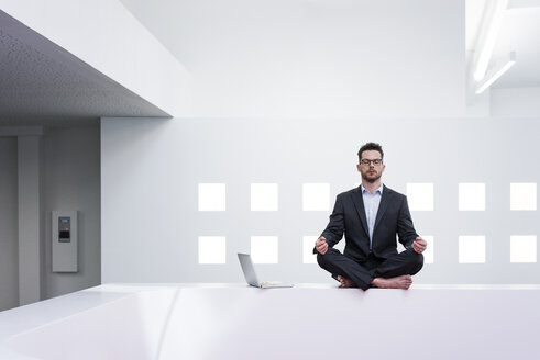 Businessman doing yoga in office next to laptop - MOEF02200