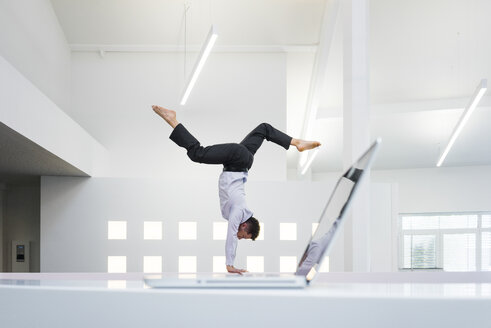 Businessman doing a handstand at laptop in office - MOEF02212