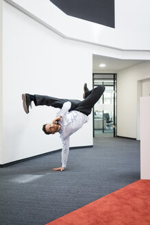 Businessman with cell phone doing a one-handed handstand on office floor - MOEF02218