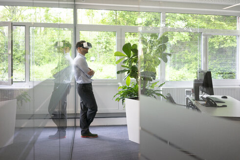 Businessman wearing VR glasses in office - MOEF02224