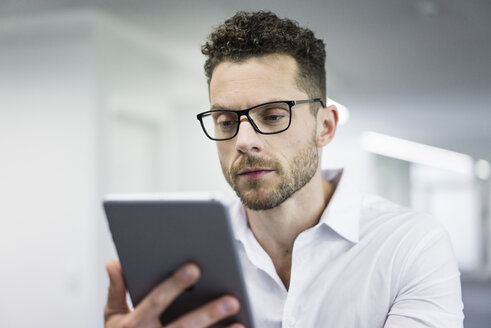 Businessman looking at tablet in office - MOEF02248