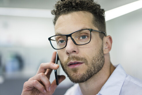 Portrait of businessman on cell phone in office - MOEF02251