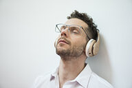 Businessman with closed eyes listening to music with headphones - MOEF02257