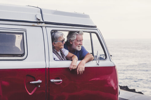 Senior couple traveling in a vintage van, looking at the sea - SIPF02003