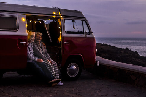 Senior couple traveling in a vintage van, watching sunset at the sea - SIPF02030