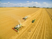 Aerial view of combine harvesters and tractor trailer in sunny golden barley field - JUIF01229
