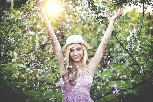 Woman standing in flowering trees - BLEF05842