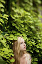 Woman standing under ivy wall - BLEF05932