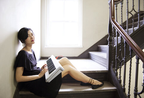 Taiwanese woman playing keyboard on staircase - BLEF06143