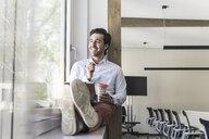 Young businessman sitting on windowsill, using digital tablet, drinking coffee - UUF17706
