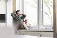 Young businessman sitting on windowsill, using laptop - UUF17715