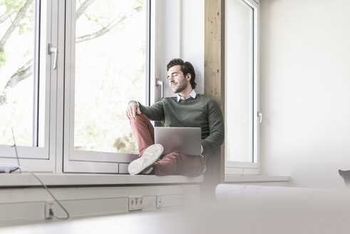 Young businessman with laptop sitting on windowsill, taking a break - UUF17718