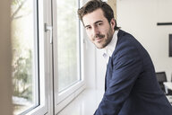 Confident businessman standing at the window - UUF17739