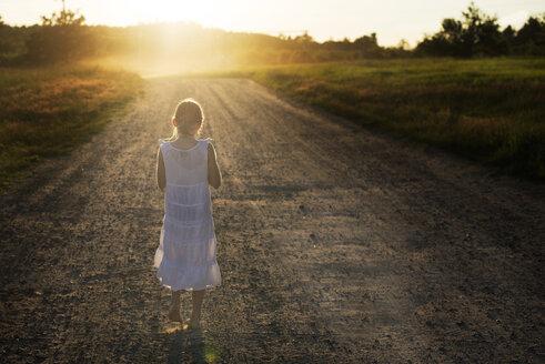 Caucasian girl walking on dirt road - BLEF06263