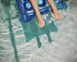Feet of Caucasian woman floating on raft in swimming pool - BLEF06335