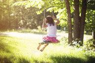 Girl playing on swing in field - BLEF06359