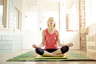 Caucasian woman meditating on yoga mat - BLEF06404