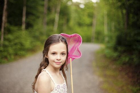 Caucasian girl carrying butterfly net on dirt road - BLEF06425