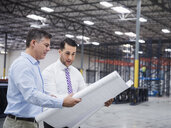 Caucasian architects reading blueprints in warehouse - BLEF06578