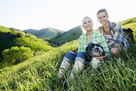 Caucasian mother and daughter petting dog on grassy hillside - BLEF06590