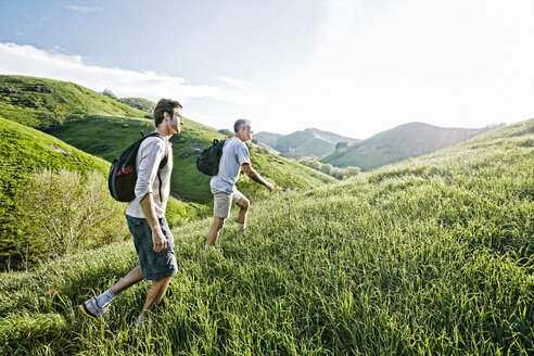 Caucasian father and son walking on grassy hillside - BLEF06648