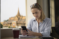 Caucasian businesswoman using cell phone in cafe, Phnom Penh, Cambodia - BLEF06663