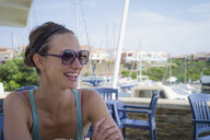 Caucasian woman smiling on restaurant patio - BLEF06675