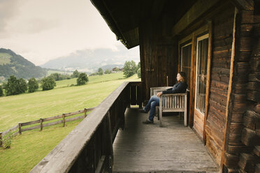 Woman sitting on balcony of rustic house, Jochberg, Austria - PSIF00275