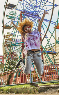 Happy woman jumping in front of a Ferris wheel - VEGF00279