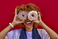Playful woman holding two donuts in front of her eyes - VEGF00282