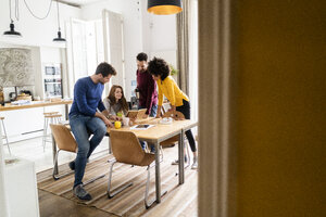 Four friends in dining room at home with book - GIOF06443
