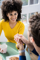 Portrait of woman holding hands and smiling at man at home - GIOF06449