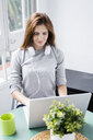 Young woman stting at table at home using laptop - GIOF06455