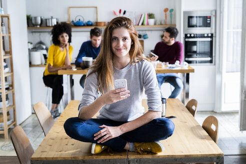 Woman with cell phone sitting on dining table at home with friends in background - GIOF06464