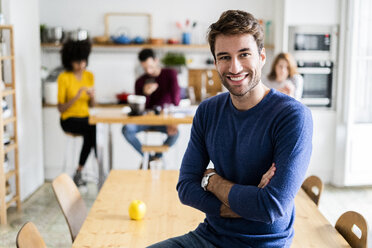 Portrait of smiling man at dining table at home with friends in background - GIOF06470