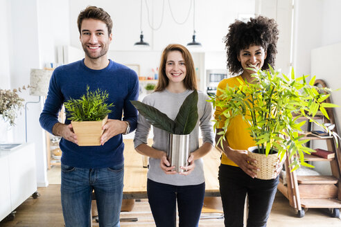 Portrait of three smiling friends holding plants at home - GIOF06476
