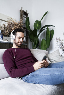 Smiling man sitting on couch with cell phone and headphones - GIOF06479