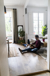 Affectionate couple with laptop relaxing on the floor at home - GIOF06491