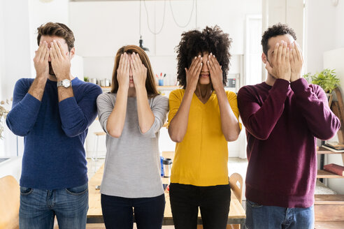 Four friends standing side by side at home covering their faces - GIOF06500