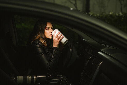 Young woman with disposable cup and camera in a car at night - LJF00107